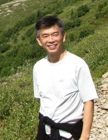 Photograph of Dr. Yang Shen, smiling on a mountainside.