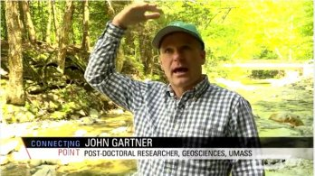 Screen capture of post-doc John Gartner speaking to camera in front of Chicklea River in Hawley, MA. John is gesturing to show height of floodwaters above his head.