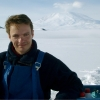 Portrait of Dr. Rob Deconto, smiling at camera in front of white snow field, with volcano in backrgound, in Antarctica