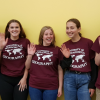 Five UMass Geography students standing in front of a yellow wall, wearing red t-shirts with U-Mass Geography logo, smiling waving at camera.